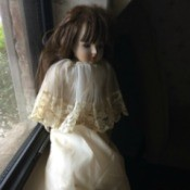 Identifying a Childhood Porcelain Doll - doll wearing an long ecru dress with matching short cape