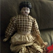 Identifying an Antique Porcelain Doll  - doll with molded hair wearing a tan and brown print dress and tan apron