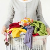 Woman holding a hamper with dirty laundry.