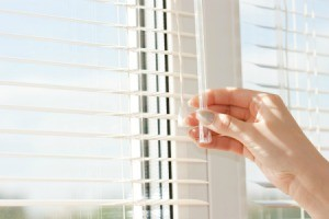 Hand adjusting horizontal blinds.
