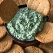 Spinach Dip surrounded by crackers.