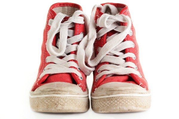 Scuffed pair of red canvas high top tennis shoes.