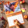 Open wall calendar with rustic October image, female hand ready to write in square with pencil.