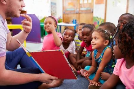 Volunteer teacher reading to a class of kids
