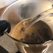 Adding hot water to the coffee grounds in the French press.