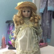 Identifying a Porcelain Doll - doll wearing a straw hat and a print dress with a lace edged apron