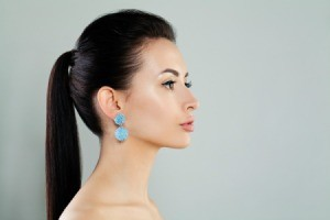 Profile of a woman with a pony tail and blue dangling earrings.