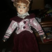 Identifying a Porcelain Doll - doll wearing a dark red dress with a floral jacket