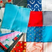 Patchwork quilt with a pile of quilting squares on top.