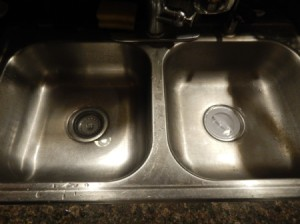 A sink with plugs in the drain and a small amount of standing water.
