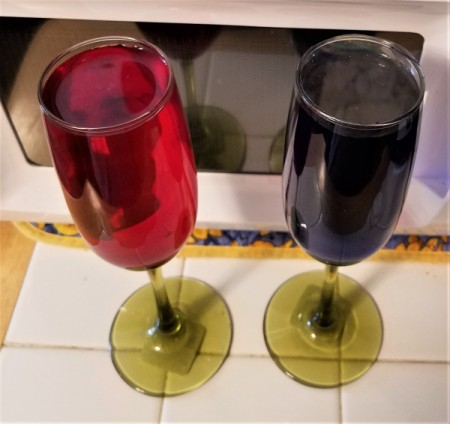 A pair of champagne flutes full of colored water.