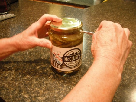 A paint key being used to open a jar of pickles.