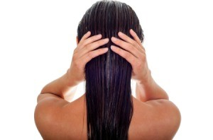 Back of woman's head holding her wet hair.