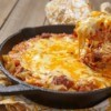 Cheesy beef casserole in a cast iron pan.