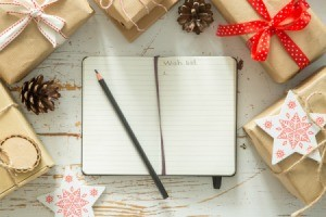 Notebook with wish list surrounded by gifts.
