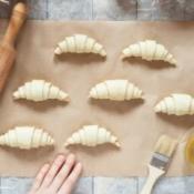 Raw croissants on parchment, preparation process.