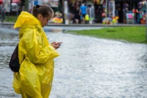 Girl in a rain poncho during a flood, using a phone.