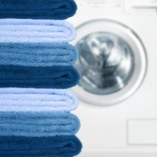 Pile of blue towels in different shades near a dryer.