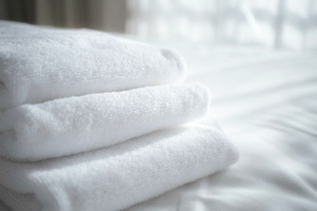 Folded white towels on a white sheet.