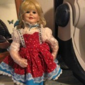Identification and Value of a Porcelain Doll - doll wearing a red print pinafore dress