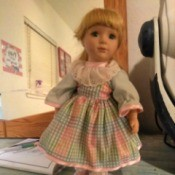 Identifying a Porcelain Doll - doll wearing a pink and blue gingham dress