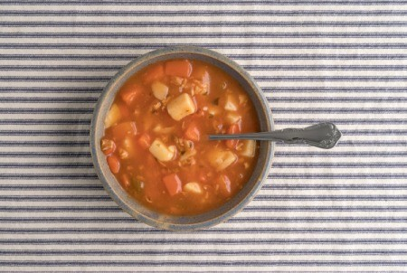 Bowl of soup on striped tablecloth.