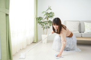 Woman cleaning floor near curtains.
