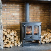 Wood Stove surrounded by cut wood.