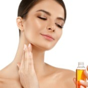 Woman putting oil on her face while holding a small bottle of oil.