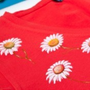 Red t-shirt painted with small daisies.
