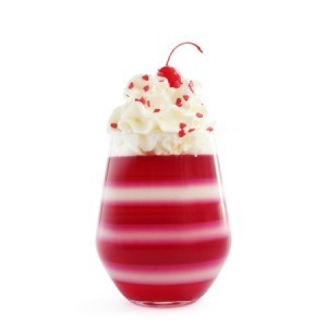 Layered jello in a glass with a cherry on top.