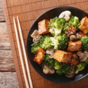 Tofu and broccoli with sesame seed in a bowl.