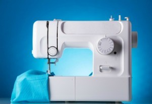 White sewing machine with a piece of blue fabric.