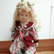 Identifying Porcelain Dolls - blonde doll wearing a floral dress with a red collar