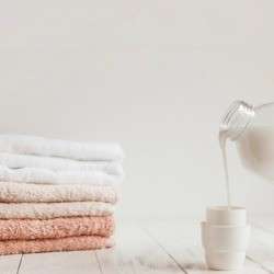 Hand pouring laundry soap into cap next to a pile of folded towels.