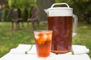 Pitcher and glass filled with ice tea on an outdoor table.