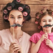 Mother and daughter with rollers and fake mustaches.