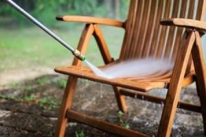 Pressure washing outdoor wooden chair.