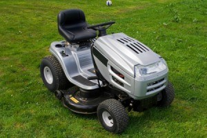Silver riding lawn mower on grass.