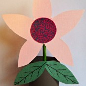 A decorative paper flower in a recycled toilet paper tube planter.