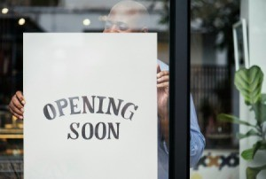 "Man putting up an ""opening soon"" sign in a storefront."
