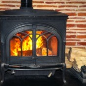 Wood stove with fire roaring inside.