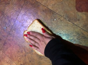 Using Bread to Pick Up Broken Glass - hand pressing a slice of bread onto a tile floor