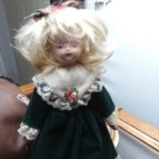 Identifying a Porcelain Doll - doll wearing a dark blue dress with lace at bottom and sleeves