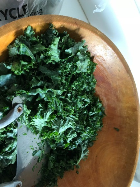 chopping kale in wooden bowl