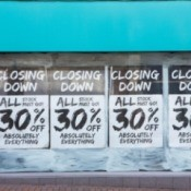 30% closing sale signs in a store window.