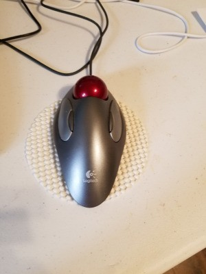 A white coaster being used under a computer mouse.