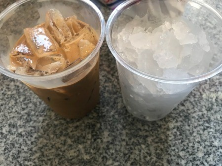 Vietnamese coffee poured into one cup with ice, with another cup with ice remains empty.