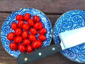 A bowl of cherry tomatoes next to a knife.