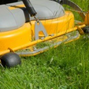 Close up of riding lawnmower cutting grass.